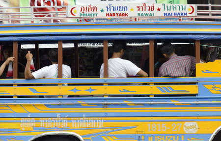PHUKET TOWN, PHUKET, THAILAND AUGUST 12 2012: Passengers sitting in a public bus at a bus depot in Phuket Town wait for departure.