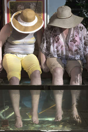 BEACH ROAD, PATONG, PHUKET, THAILAND: FEBRUARY 23 2012: Two western tourists get a fish pedicure at a street side massage parlor.
