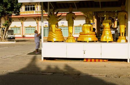 thai motifs: WAT KARON MARKET, KARON, PHUKET, THAILAND FEBRUARY 8 2013: A tourist snaps a photo of a row of Buddha statues in the courtyard of Temple Karong in Phuket .