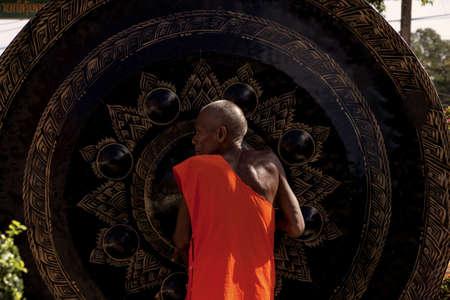 WAT KARON MARKET, KARON, PHUKET, THAILAND FEBRUARY 8 2013: A monk in the courtyard of Temple Karong in Phuket rubs a large gong to make it ring.  Stock Photo - 20264087