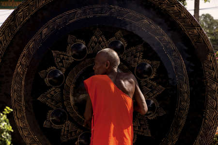 resonating: WAT KARON MARKET, KARON, PHUKET, THAILAND FEBRUARY 8 2013: A monk in the courtyard of Temple Karong in Phuket rubs a large gong to make it ring.