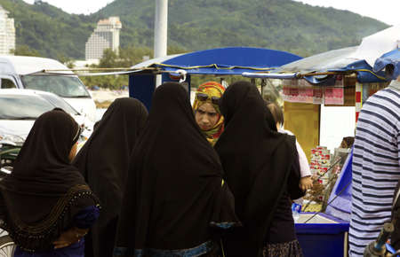 KALIM BEACH, PHUKET, THAILAND APRIL 15 2013: A group of Thai Muslim women chat while buying food at a concession stand along Kalim Beach in Phuket.