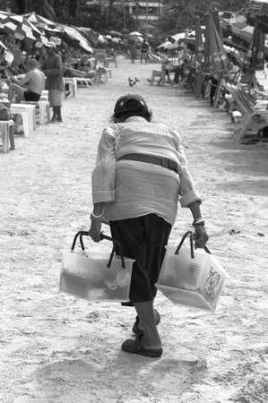 abnormal: PATONG BEACH, PHUKET, THAILAND DECEMBER 11 2010: An elderly beach peddler sells beverages and snacks on Patong Beach.