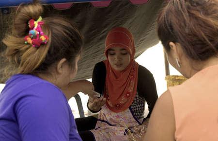phuket food: KALIM BEACH, PHUKET, THAILAND APRIL 15 2013: Muslim food vendor makes change for customers at her market stall.