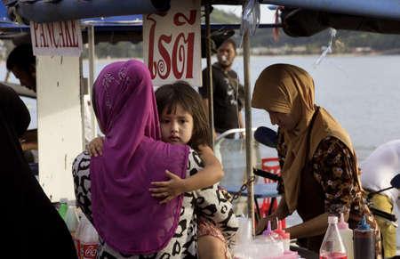 phuket food: KALIM BEACH, PHUKET, THAILAND JAPRIL 15 2013: Mom and daughter buy some Thai style pancakes at food stall.