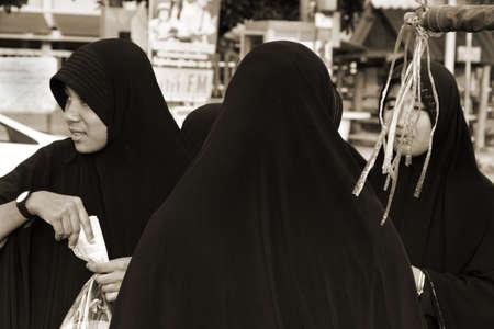 concession: KALIM BEACH, PHUKET, THAILAND APRIL 15 2013: A group of Thai Muslim women buy snacks at a concession stand along Kalim Beach in Phuket.