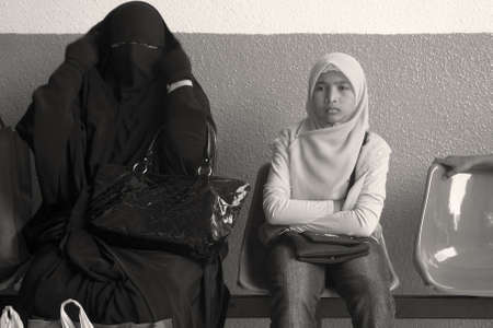 burqa: GENTING HIGHLANDS, MALAYSIA OCTOBER 16 2009: A Muslim woman in full burqa sits next to a Malaysian child in a hijab at a bus depot in Genting Highlands.  Editorial