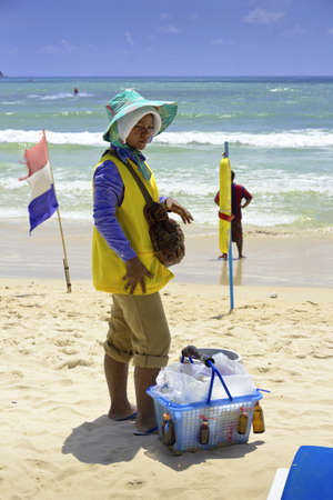 clothed: PATONG BEACH, PHUKET, THAILAND AUGUST 11 2011: A beach vendor is fully clothed to protect herself against the hot sun while she works.