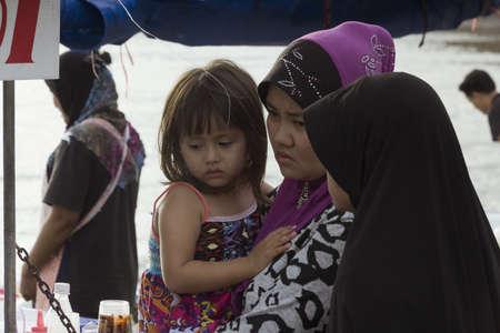 phuket food: KALIM BEACH, PHUKET, THAILAND APRIL 15 2013: Mom and daughter buy some Thai style pancakes at food stall.  Editorial