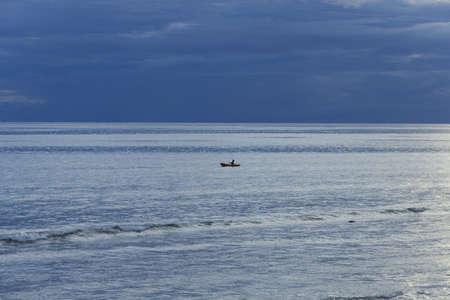 KALIM BEACH, PHUKET, THAILAND APRIL 15 2013: A man in a row boat paddles across the bay  at twilight off Kalim Beach.