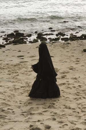 burqa: KALIM BEACH, PHUKET, THAILAND APRIL 15 2013: A Thai Muslim woman takes a walk along Kalim Beach in Phuket.