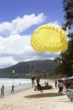 PATONG BEACH, PHUKET, THAILAND, AUGUST 4 2011: A parasail operator lands with a customer after a ride on Patong Beach.