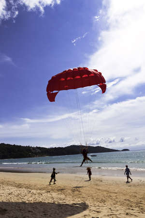 PATONG BEACH, PHUKET, THAILAND, AUGUST 18 2011: A parasail vendor prepares to recover a customer landing on Patong Beach. Editorial