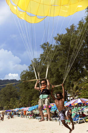 PATONG BEACH, PHUKET, THAILAND, AUGUST 23 2011: A parasail operator lands with a customer after a ride on Patong Beach. Editorial