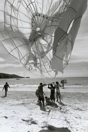 PATONG BEACH, PHUKET, THAILAND, AUGUST 23 2011: Parasail operators untangle a customer from a canopy