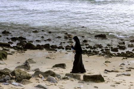 burqa: KALIM BEACH, PHUKET, THAILAND APRIL 15 2013: A Thai Muslim woman texts on her mobile while walking along Kalim Beach in Phuket.