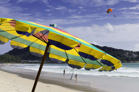 PATONG BEACH, PHUKET, THAILAND, AUGUST 3 2011: A parasail operator soars high above the sand with a customer during a ride on Patong Beach.
