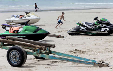 PATONG, PHUKET, THAILAND AUGUST 16 2011: A boy sprints past parked jet skis on Patong Beach. Editorial