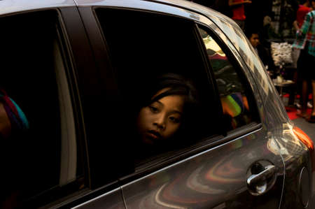 soi: PATONG, PHUKET, THAILAND, 26 FEBRUARY 2011: A young girl watches a post-parade celebrationfrom the backseat of a carparty in Soi Paradise at the annual Patong Gay Pride Parade . Editorial