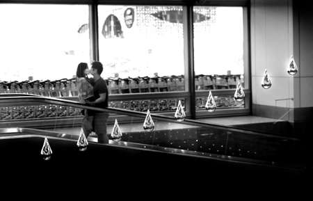 reportedly: CHANGI AIRPORT, SINGAPORE, 20 MAY 2014: Two lovers share a kiss under Kinetic Rain, a hanging, moving sculpture at Changi Airport and reportedly the largest kinectic art sculpture in the world.