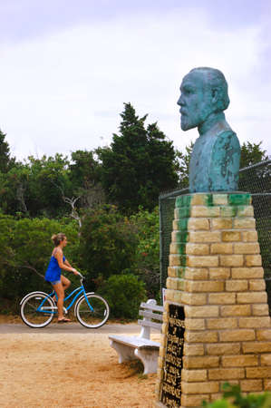 BARNEGAT LIGHTHOUSE, NEW JERSEY SHORE, USA, 10 JULY 2010: Cyclist rides past bust portrait of General George Meade.
