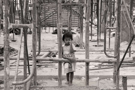 PHUKET, THAILAND, 23 FEBRUARY 2012: A young girl plays inside a construction site surrounded by a bamboo frame. Editorial