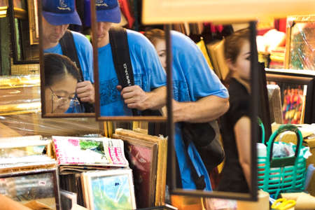 CHATUCHAK MARKET, BANGKOK, THAILAND: 18 MARCH 2012: Tourists shop at Chatuchak Weekend Market in Bangkok.