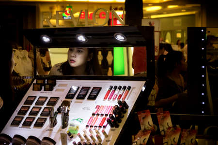full length mirror: JUNGCEYLON MEGAMALL, PHUKET, THAILAND, 27 DECEMBER 2013: A Thai woman tries on some make-up at a kiosk in a shopping center.