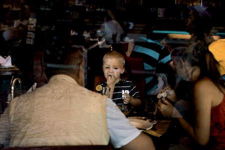 phuket food: PHUKET, THAILAND, 1 MARCH 2012: Boy on holiday enjoys Thai food at restuarnt with mom and dad.