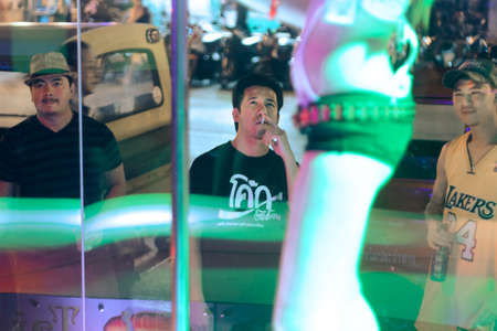 BANGLA ROAD, PATONG BEACH, PHUKET, THAILAND, 12 MARCH 2012:  Tourists watch a nightclub dancer pole dance in Patong Beach.