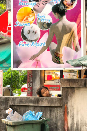 PHUKET, THAILAND, 18 OCTOBER 2011: A little girl pauses to rest under a billboard whilst playing.