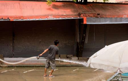 BANZAAN ROAD, PATONG BEACH, PHUKET, THAILAND, 7 AUGUST 2013: A municipal worker washes down a city street in Phuket.