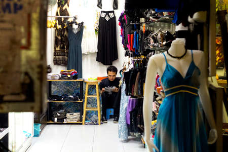 BANGLA RD., PATONG, PHUKET, THAILAND, 22 MAY 2012: A shop owner goes online while working in his store.