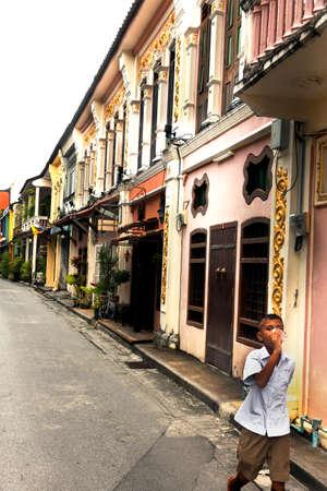 soi: SOI ROMANEE, OLD TOWN PHUKET, PHUKET, THAILAND, 6 JULY 2012: Schoolboy enjoys a drink after school on Soi Ramonee. Editorial