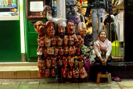 novelties: BANGLA RD., PATONG, PHUKET, THAILAND, 28 MAY 2012: A street peddler sells Halloween and party masks on Soi Bangla. Editorial