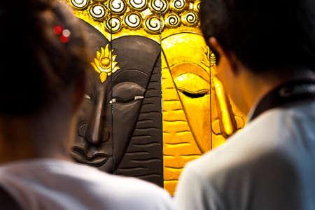 triptico: BANGKOK, TAILANDIA, 18 de marzo 2012: mirada pareja occidental en un tríptico budista a la venta en un mercado de la calle de Bangkok.