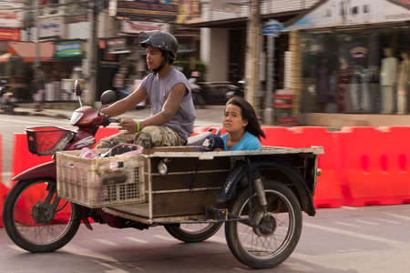 sidecar: PHUKET, THAILAND, 7 MAY 2012: Thai woman with her child rides in a motorbike sidecar.