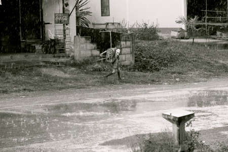 KALASIN PROVINCE, NORTHEAST (ISSAN) THAILAND, 16 JULY 2012: An elementary school lad sprints through the rain at the end of the school day.