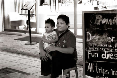 BANGLA ROAD, PATONG, PHUKET, THAILAND, 23 MAY 2012: A mother works a street vendor