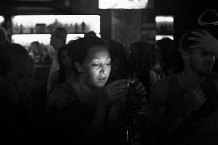 BANGLA RD., PATONG, PHUKET, THAILAND, 9 MAY 2012: A  woman out clubbing checks her camera after taking a snapshot.