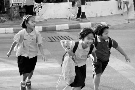 PHUKET, THAILAND, 15 FEBRUARY 2012: A group of Thai school girls run across the street at the end of the school day.