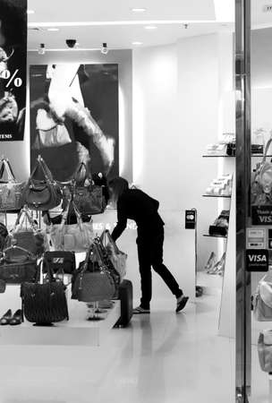 JUNGCEYLON MEGAMALL, PHUKET, THAILAND, 28 MAY 2012: A salesperson arranges a display in a shoe boutique at an upscale shopping mall in Thailand.