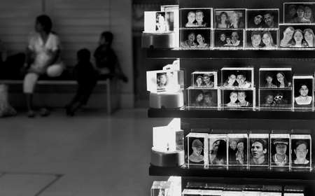 SHOPPING MALL KIOSK, PHUKET; THAILAND; 12 JULY 2012: A family sits behind a display of acrylic blocks with photos of tourists past. 報道画像
