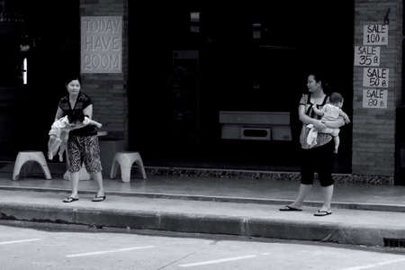 PATONG BEACH, PHUKET, THAILAND, 1 JUNE 2012: Two Thai mothers hold their babies on the street in front of a guesthouse.