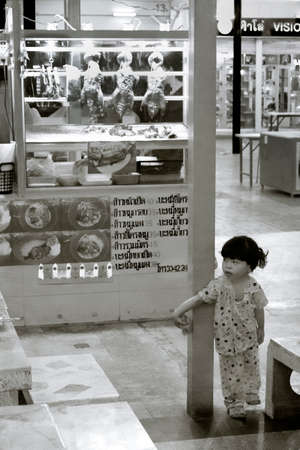 UDON THANI, THAILAND, 15 JULY 2012: The daughter of a food vendor at a night market plays past her bedtime. 報道画像