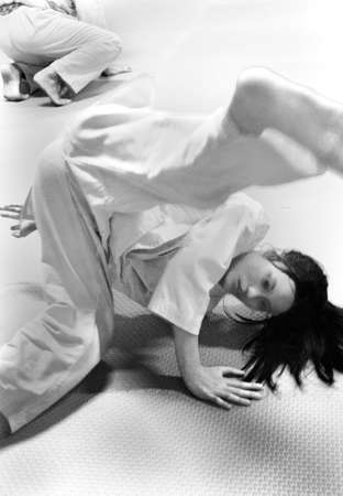 PHUKET TOWN, PHUKET, THAILAND, 3 MARCH 2014: A young Thai college student warms up before her Aikido promotion test.