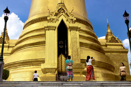 GRAND PALACE, BANGKOK, THAILAND, 26 SEPTEMBER 2014: Chinese tourists pose for holiday a snapshot under a large stupa at the Grand Palace in Bangkok. Editorial