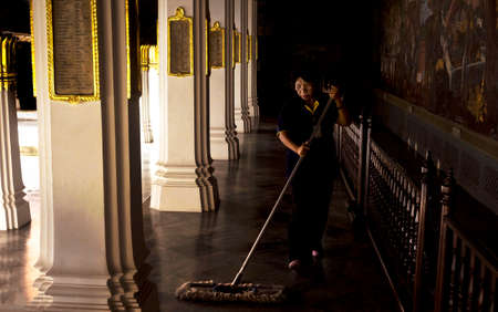 groundskeeper: GRAND PALACE, BANGKOK, THAILAND, 26 SEPTEMBER 2014: A groundskeeper dusts a marble corridor at the Grand Palace in Bangkok