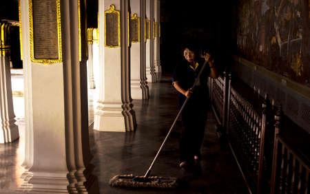groundskeeper: GRAND PALACE, BANGKOK, THAILAND, 26 SEPTEMBER 2014: A groundskeeper dusts a marble corridor at the Grand Palace in Bangkok