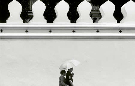 GRAND PALACE, BANGKOK, THAILAND, 26 SEPTEMBER 2014: A couple hold a sun umbrella as they walk past the perimeter wall of the Grand Palace in Bangkok. Editorial